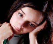 A young woman looking sad and holding her head in her hand. Ref: www.dreamstime.com