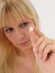 A young blonde-haired woman holding up a white tablet. Ref www.dreamstime.com