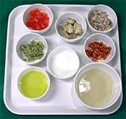 A selection of foods in white bowls on a white tray. Ref: www.dreamstime.com