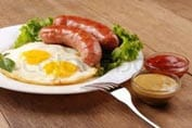 Two fried eggs, two sausages and some lettuce on a plate. Ref: www.dreamstime.com