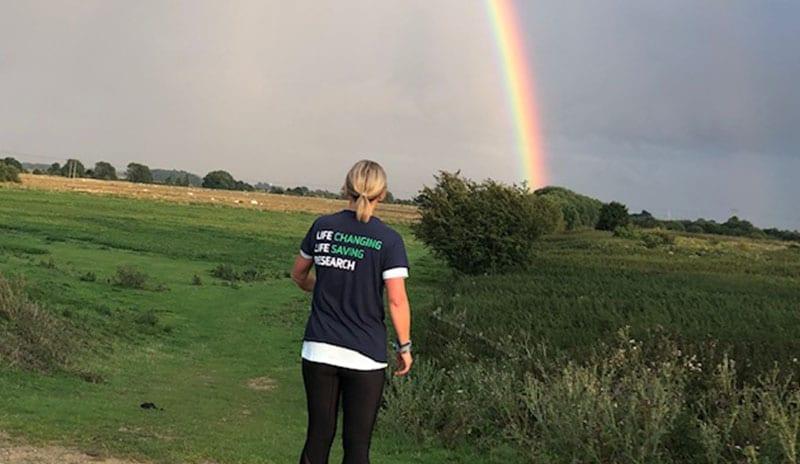 Woman walking across field by rainbow